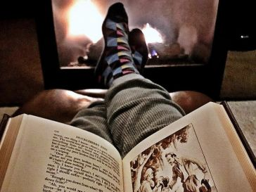 Book on a lap in front of a glowing fireplace (Reproduced with permission: https://www.flickr.com/photos/phoenixreguy/2708924923