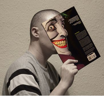 An image of a person holding 'The Killing Joke' in front of their face Photo by Flickr User Ben Watkin
