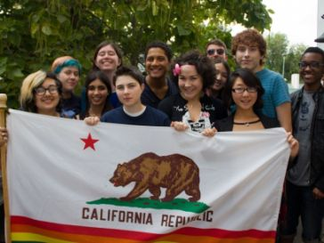 Youth holding a California State Flag with Rainbow detail
