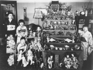 Japanese Children posing with a case of dolls and medals