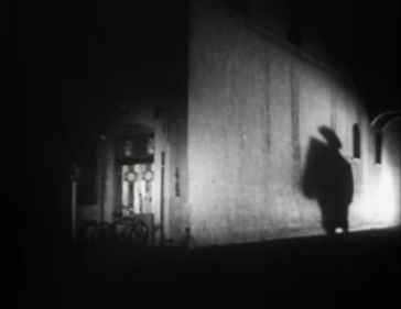 A picture of a person's shadow projected on the wall of an alley from Public Domain