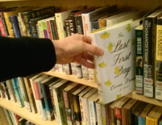 A book being pulled from the shelf.